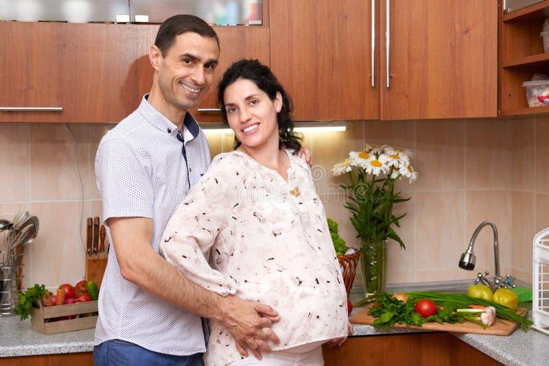Dobiera się w kuchennym wnętrzu z świeżymi owoc i warzywo, zdrowym karmowym pojęciem, kobieta w ciąży i mężczyzna, obrazy royalty free