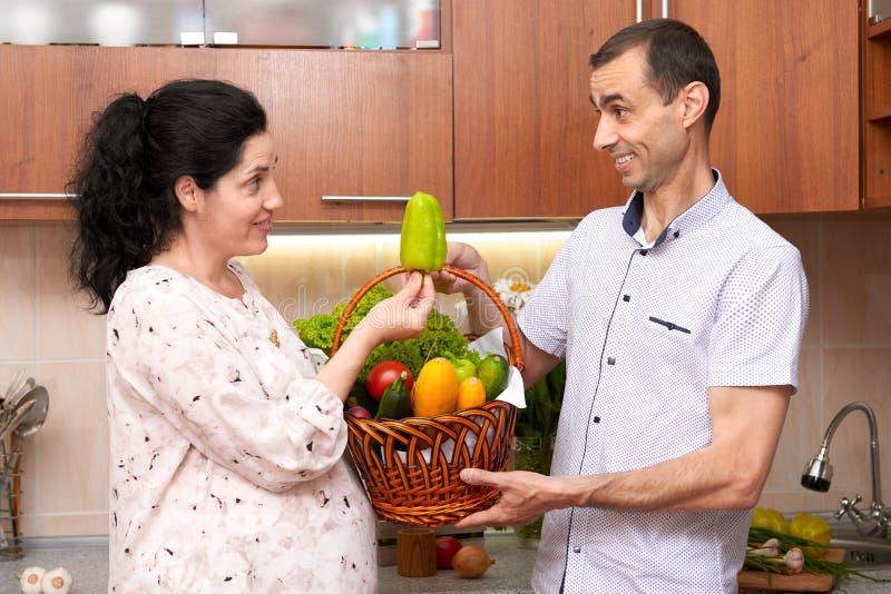 Dobiera się w kuchennym wnętrzu z koszem świezi owoc i warzywo, zdrowy karmowy pojęcie, kobieta w ciąży i mężczyzna, zdjęcie royalty free