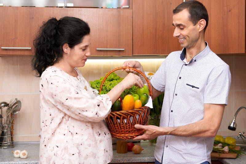 Dobiera się w kuchennym wnętrzu z koszem świezi owoc i warzywo, zdrowy karmowy pojęcie, kobieta w ciąży i mężczyzna, obrazy stock