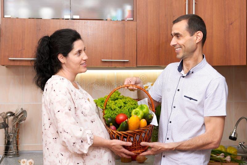 Dobiera się w kuchennym wnętrzu z koszem świezi owoc i warzywo, zdrowy karmowy pojęcie, kobieta w ciąży i mężczyzna, fotografia royalty free