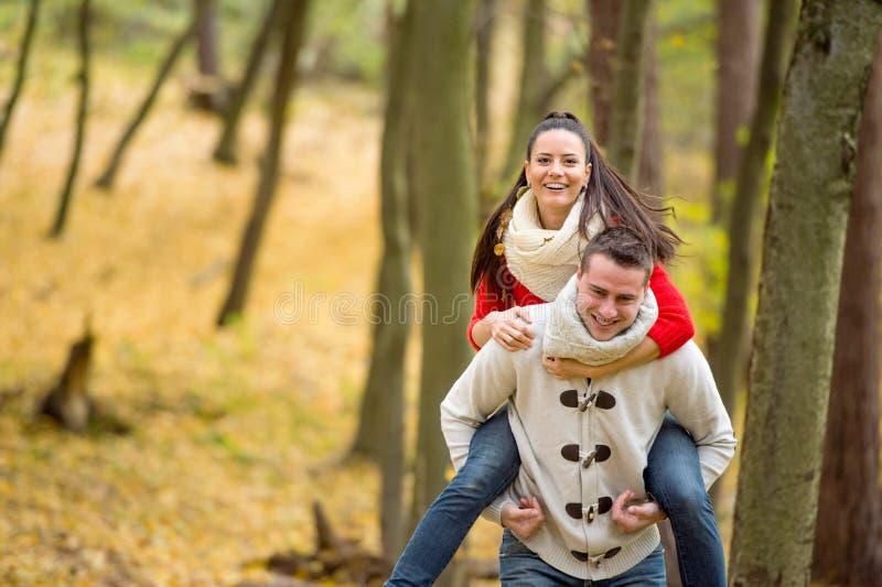 Dobiera się w miłości, mężczyzna daje jego kobiecie piggyback zdjęcie stock