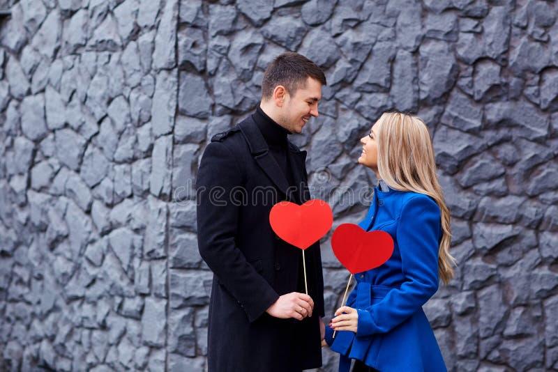 Dobiera się z czerwonym sercem w jego rękach na tle obrazy stock