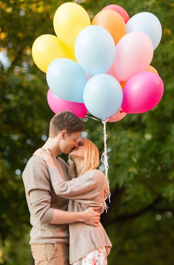 Dobiera się z kolorowymi balonami całuje w parku fotografia royalty free