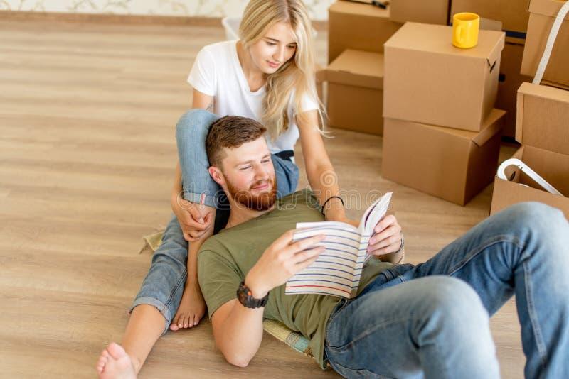 Dobiera się z książkowym obsiadaniem na łóżku podczas gdy ruszający się w nowego dom obrazy royalty free