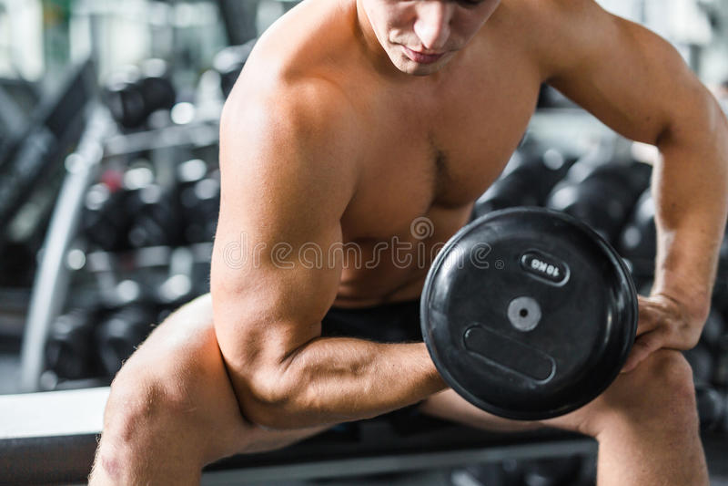 Doblar los músculos del brazo en el entrenamiento de la fuerza foto de archivo libre de regalías