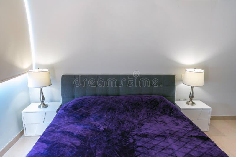 Doble-cama con una sobrecama violeta en el interior Reparación moderna fotografía de archivo libre de regalías