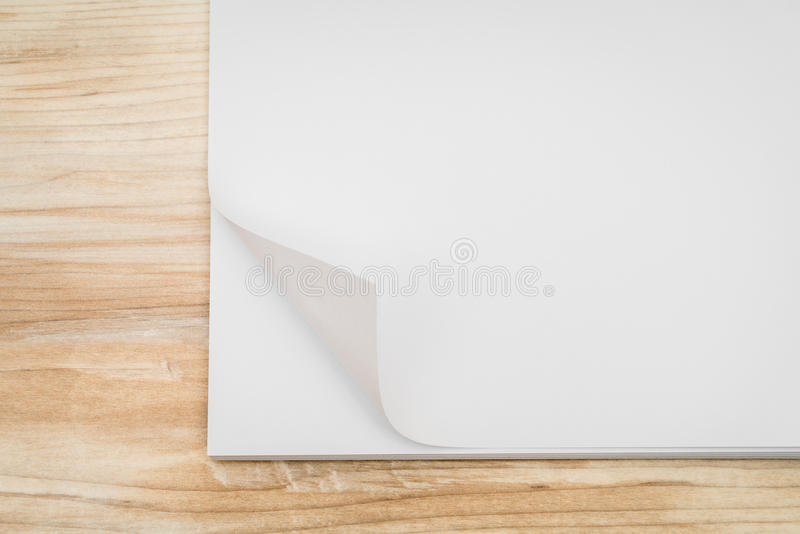 Doblez de la esquina de papel real en el fondo de madera imagenes de archivo