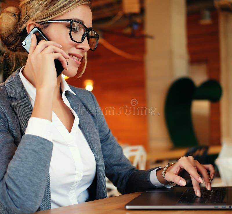 Dobra biznesowa rozmowa Młoda piękna kobieta opowiada na m w szkłach obrazy royalty free