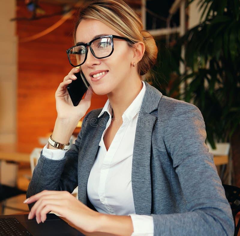 Dobra biznesowa rozmowa Młoda piękna kobieta opowiada na m w szkłach zdjęcia stock