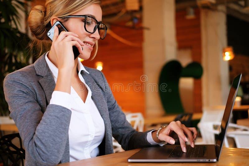 Dobra biznesowa rozmowa Młoda piękna kobieta opowiada na m w szkłach zdjęcia royalty free