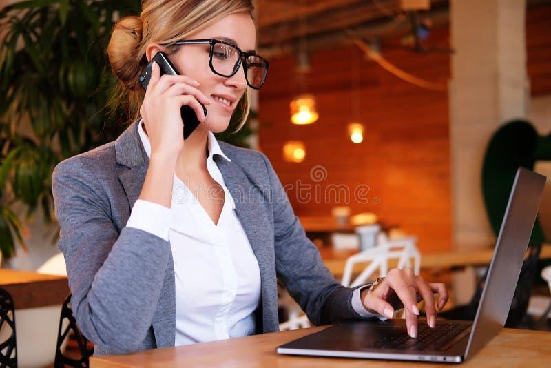 Dobra biznesowa rozmowa Młoda piękna kobieta opowiada na m w szkłach fotografia royalty free