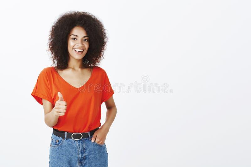 Dobra praca, dziewczyna Ufna zadowolona atrakcyjna kobieta z afro fryzurą trzyma rękę w kieszeni i pokazuje aprobaty, zdjęcie royalty free