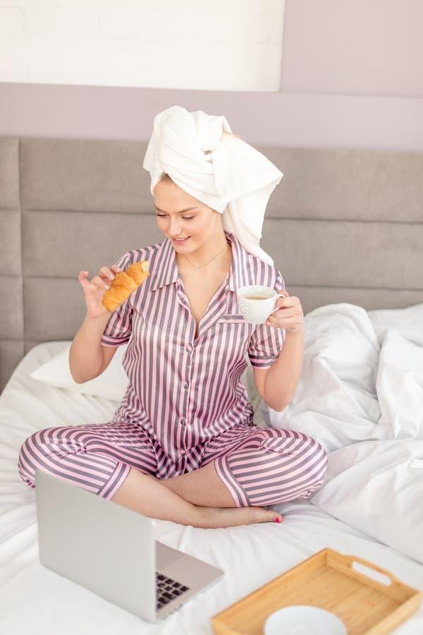 Dobra przyglądająca dziewczyna cieszy się śniadanie w sypialni obrazy royalty free
