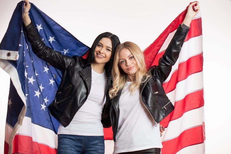 Dobra przyglądająca brunetka i blondynka trzymamy usa flaga zdjęcia stock