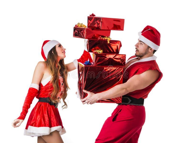 Dobra przyglądająca para w Święty Mikołaj kapeluszu z Bożenarodzeniowym prezentem obrazy royalty free