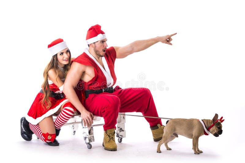Dobra przyglądająca para w Święty Mikołaj kapeluszu z Bożenarodzeniowym prezentem obraz stock