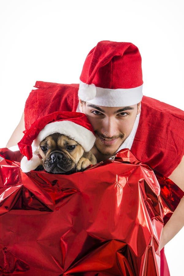 Dobra przyglądająca para w Święty Mikołaj kapeluszu z Bożenarodzeniowym prezentem fotografia royalty free