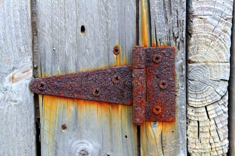 A dobradiça envelhecida oxidada do ferro resistiu à porta de madeira cinzenta foto de stock
