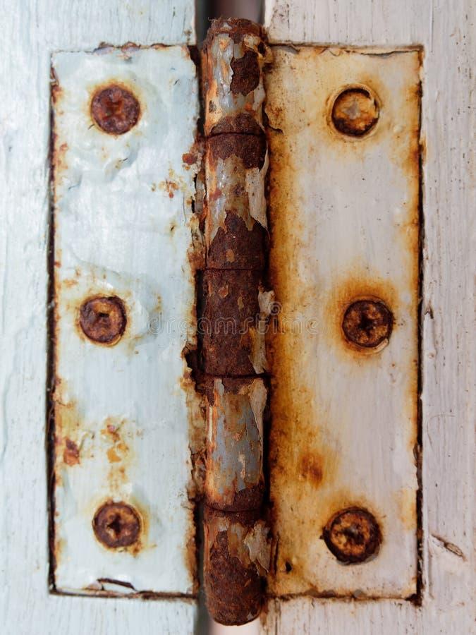 Dobradiça rústica velha do metal com o parafuso sobre a janela de madeira branca no estilo do grunge, o retro, e do vintage fotografia de stock