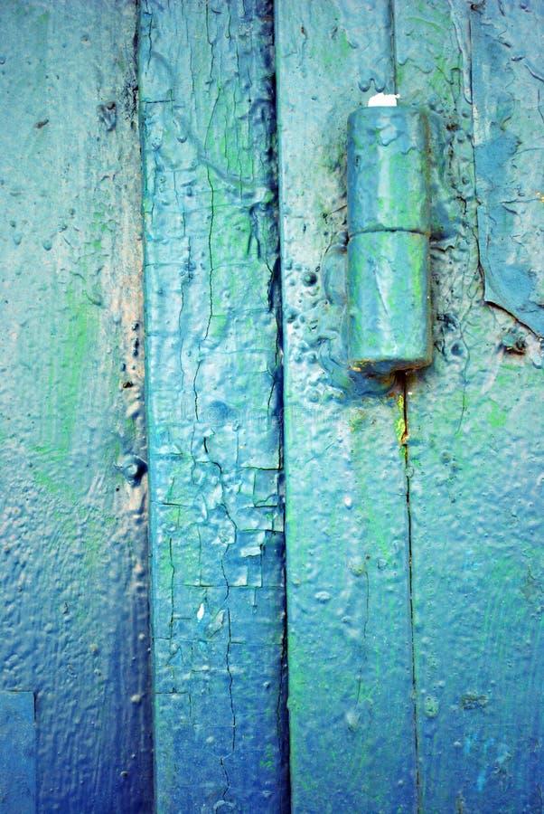Dobradiças na porta velha com um azul de turquesa gasto, pintura verde do ferro imagens de stock royalty free