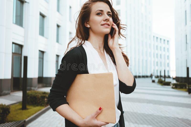 Dobrador disponivel e seguranças entre o espaço urbano e fala do original da posse nova da mulher de negócios no smartphone fotos de stock royalty free