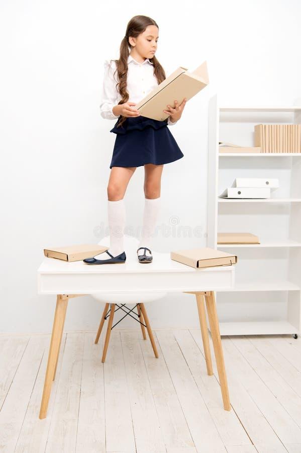 Dobrador do arquivo do trabalho da tabela do suporte da estudante Leitor ávido pequeno bonito O aluno que estuda a história leu o foto de stock