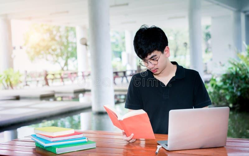 Dobrador do livro de escola da leitura do estudante do homem novo foto de stock royalty free