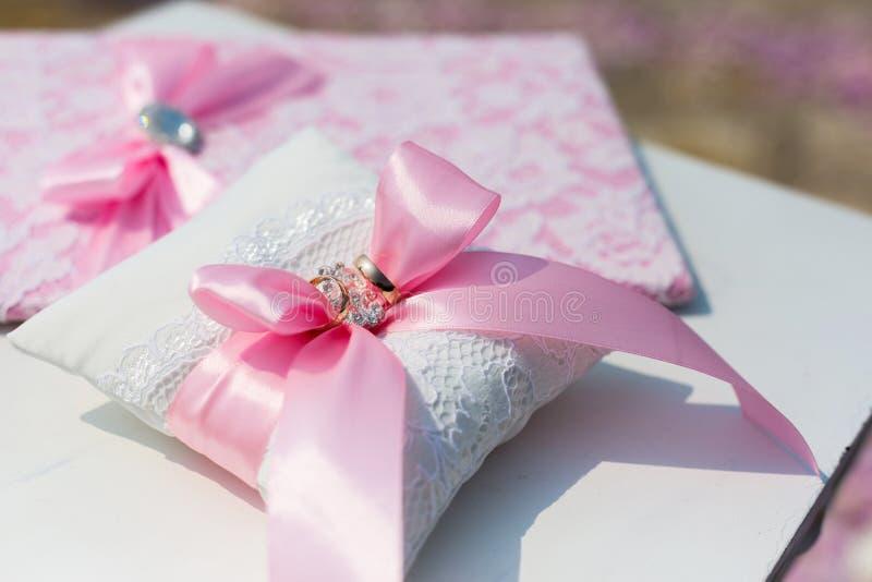 Dobrador e descanso do casamento com anéis imagens de stock royalty free