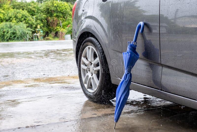 Dobradura azul próxima do guarda-chuva com carro cinzento fotografia de stock