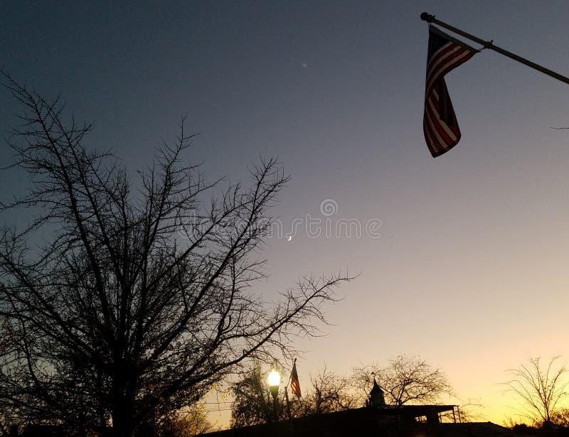 Dobranoc - miasteczko zmierzch z drzewnymi sylwetkami i dwa flagami amerykańskimi fotografia stock