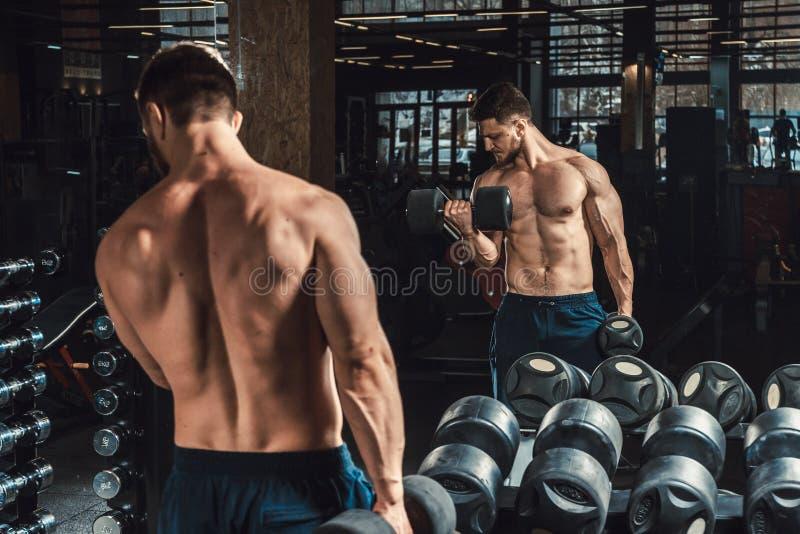 Dobrego przyglądającego młodego człowieka podnośni dumbbells i działanie na jego bicepsach przed lustrem patrzeje na jego bicepsa fotografia stock