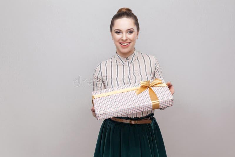 Dobroci atrakcyjna młoda dorosła kobieta w bielu z zielonej liny spódnicową pozycją dawać ci teraźniejszości z żółtym łękiem i i  fotografia royalty free