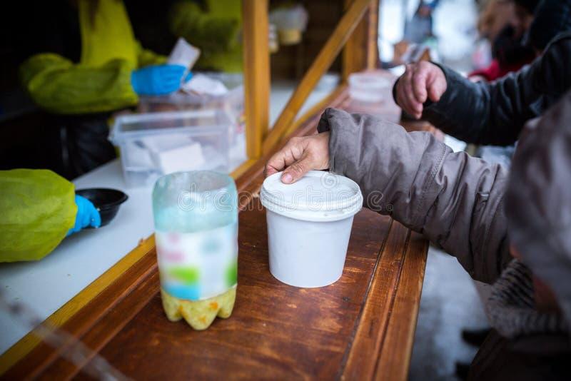 dobroczynno?? Walka przeciw ubóstwu Wolontariuszi wręczający za gorących posiłkach ludzie w potrzebie zimna dzie? zima zdjęcie stock