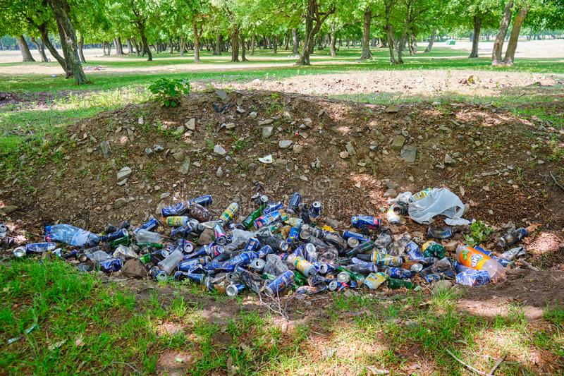 Man made garbage pile in nature. Aluminium beer and soda cans, and a few plastic bottles thrown on the ground in a pit. Dobrogea, Romania - May 19, 2019: Man stock image
