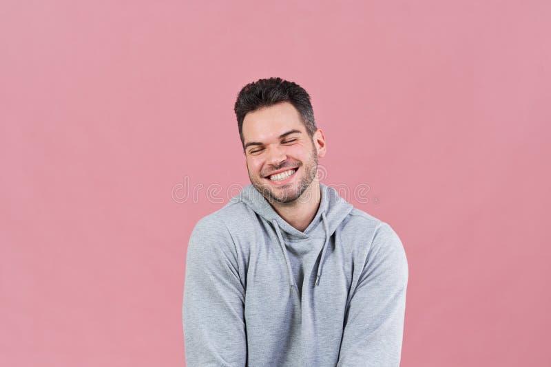 Dobrotliwy atrakcyjny młody człowiek confusedly zamyka i pojęcie pozytyw, wprawiać w zakłopotanie, śmieszne emocje na twarzy, zdjęcie stock