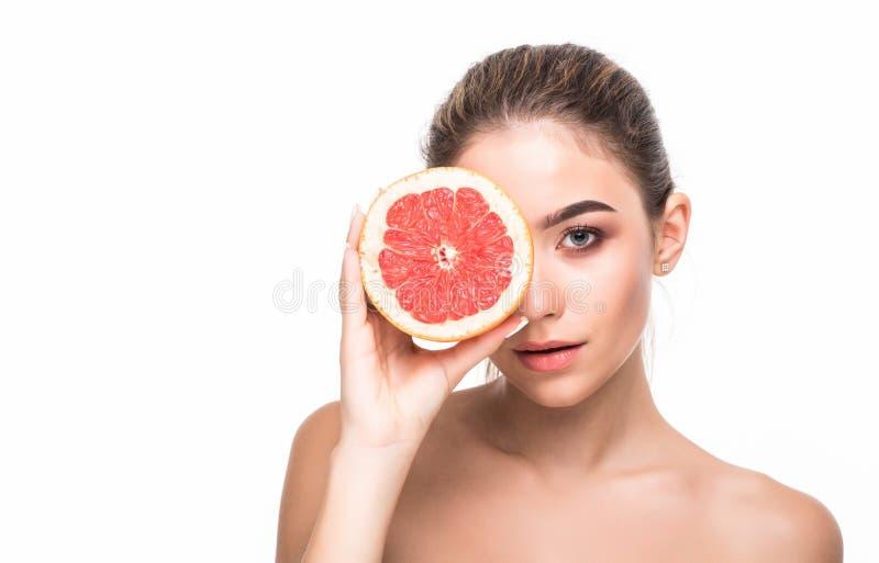 Dobry dla mój skóry Młoda atrakcyjna kobieta trzyma kawałek pomarańczowa grapefruitowa pokrywa ona oczy i ono uśmiecha się odizol fotografia stock