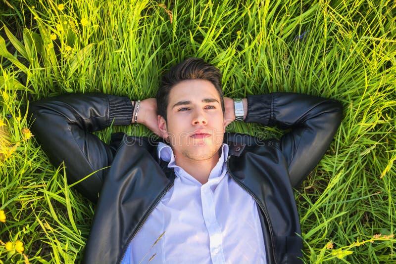 Dobry patrzeć, dysponowanego samiec modela relaksujący lying on the beach na zdjęcie royalty free
