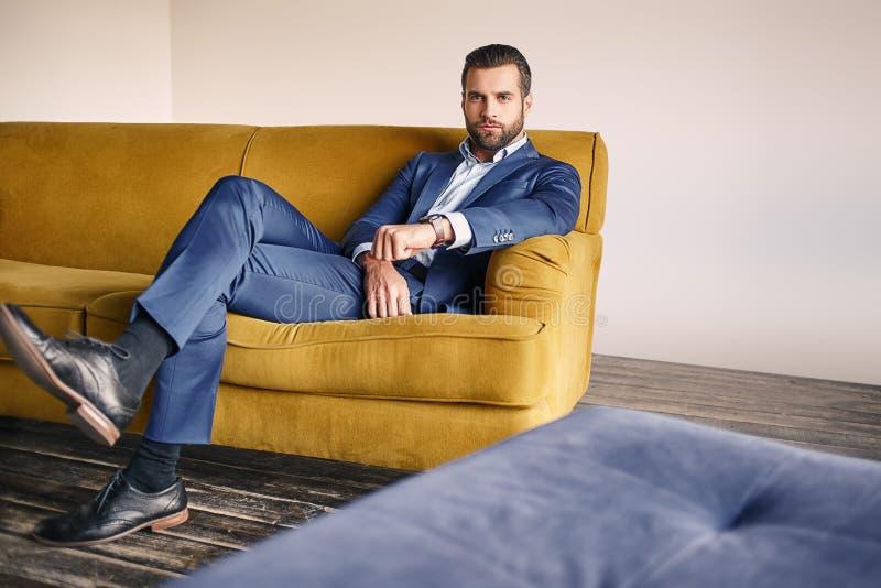 Dobry przyglądający młody biznesmen w eleganckim kostiumu jest relaksujący na kanapie i patrzeć kamerę fotografia stock