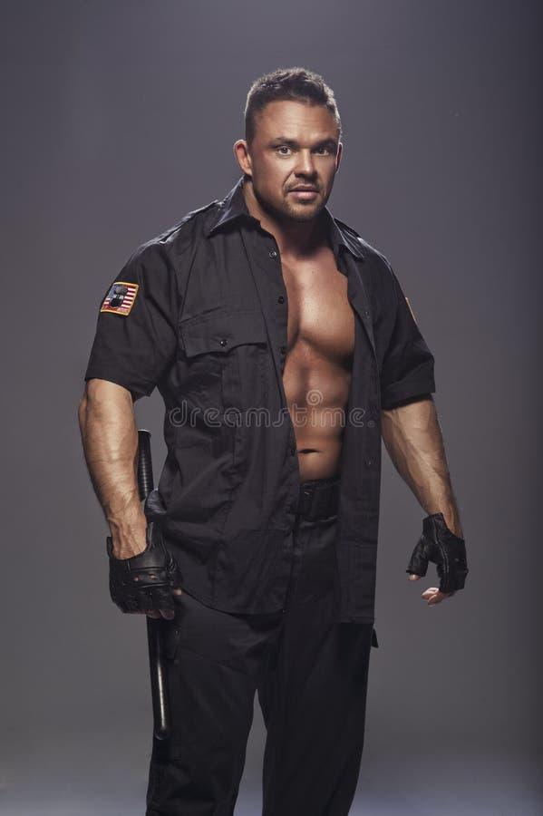 Dobry przyglądający policjanta bodybuilder pozować obraz stock