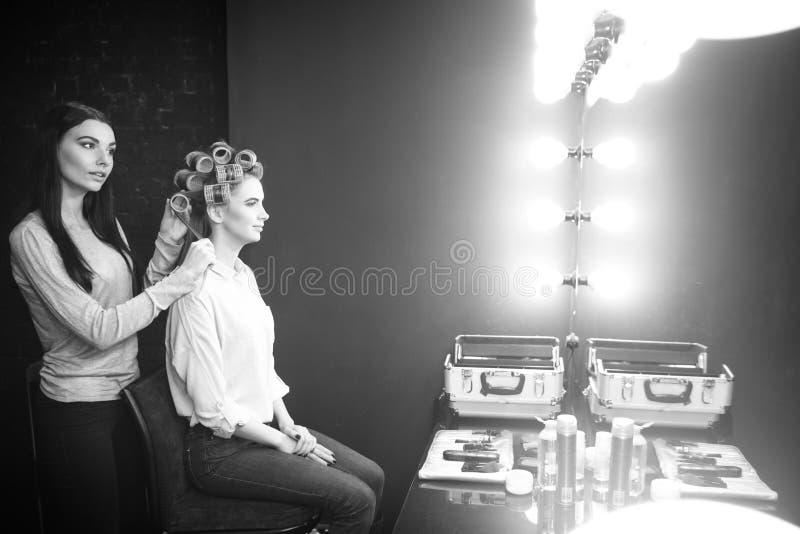 Dobry przyglądający sprawny fryzjer używa włosianych curlers fotografia stock