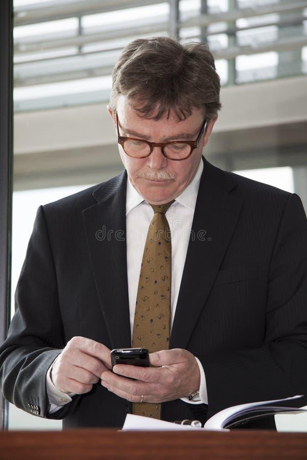 Dobrze dreassed biznesmen przy biurowym biurkiem texting na jego telefonie komórkowym w nowożytnym budynku fotografia royalty free