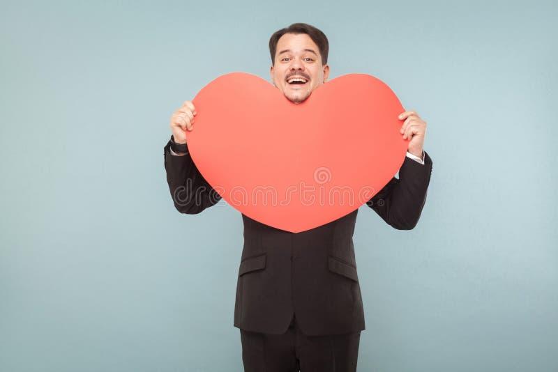 Dobrze ubierający dorosły mężczyzna trzyma dużych czerwonych ono uśmiecha się i serce fotografia stock