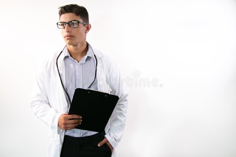 Dobrze wyglądający lekarz noszący płaszcz laboratoryjny, trzymający schowek i odwracający uwagę od kamery w tle obraz royalty free