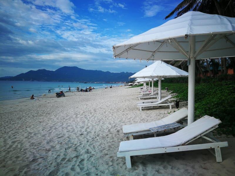 Doc. Let van het Docletstrand in Nha Trang Vietnam kust witte sunbeds en paraplu's door het overzees stock foto's