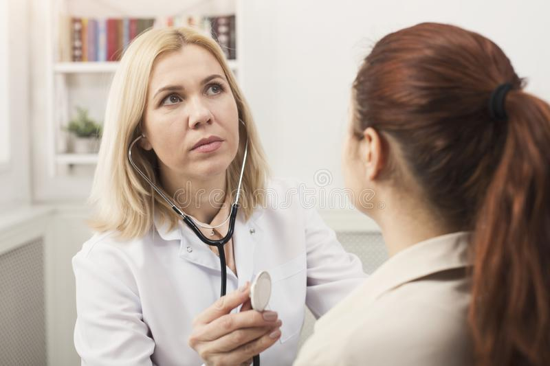 Doc with stethoscope checking patient heart beat stock photo