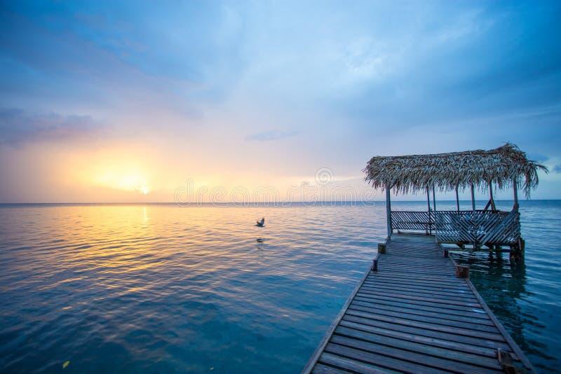 Doca com um telhado do palapa durante o por do sol e a água azul calma fotografia de stock