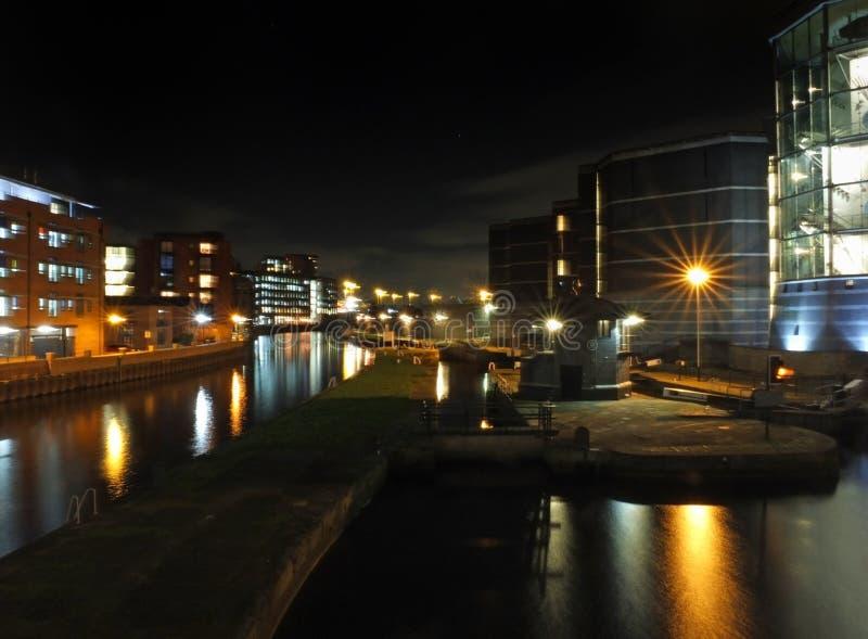 Doca de Clarence em leeds na noite com construções da cidade refletida na água fotografia de stock
