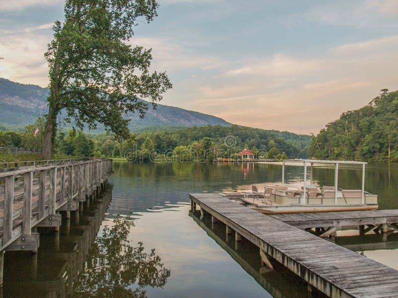 Doca do barco da atração do lago no por do sol foto de stock