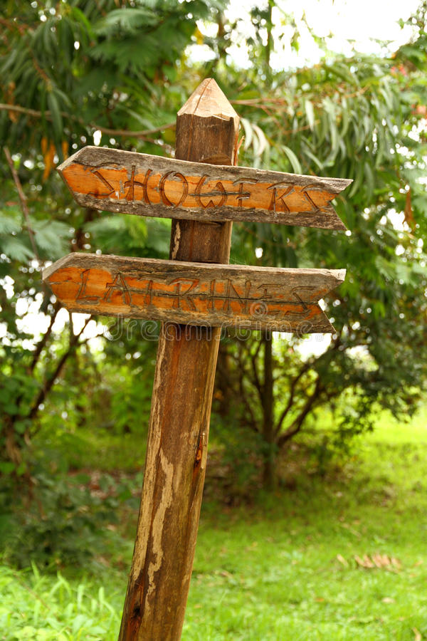 Docce e segno di legno delle latrine vecchio fotografie stock