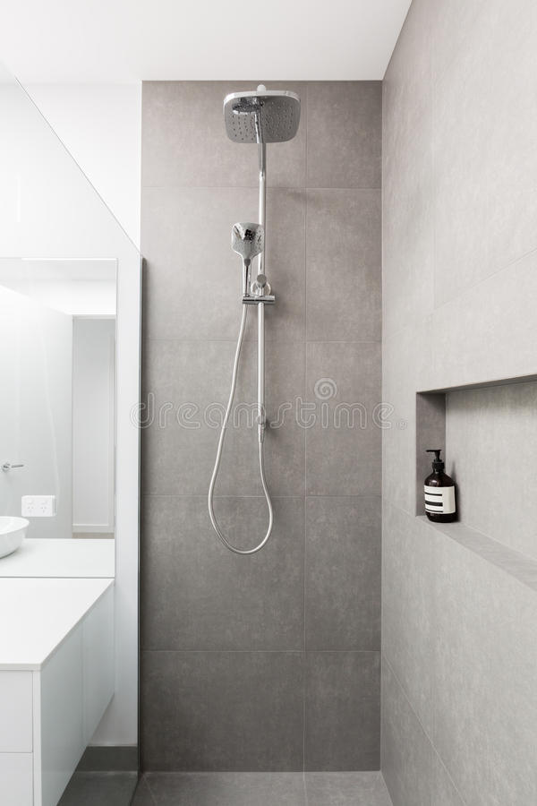 Doccia completamente piastrellata del lusso con la testa della pioggia e la doccia tenuta in mano immagine stock